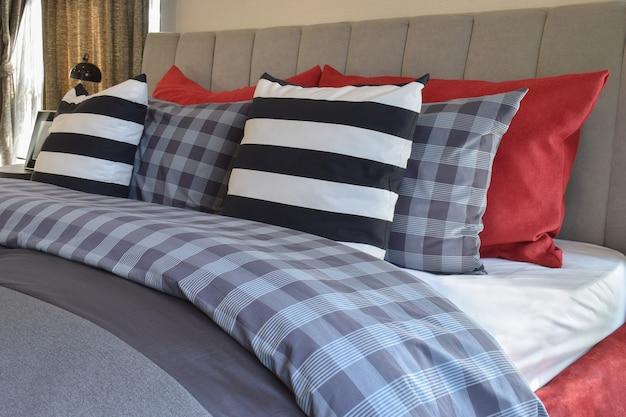 Interno camera da letto moderna con cuscino a strisce sul letto