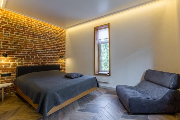 Camera da letto moderna in stile loft con letto grande in colore scuro