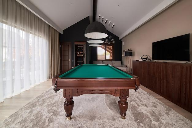 Moderna sala biliardo con un bel tavolo e ampie finestre.