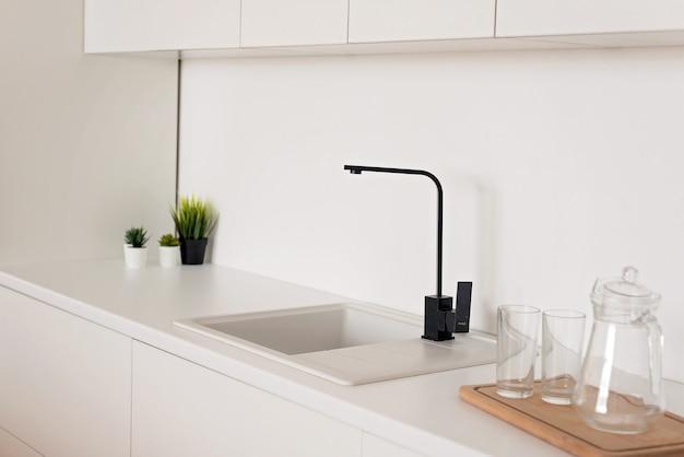 Rubinetto nero moderno in un lavello da cucina bianco. messa a fuoco selettiva morbida.