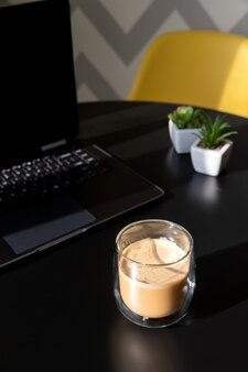 Tavolo da cucina nero moderno con il computer portatile, la tazza di caffè e le piante