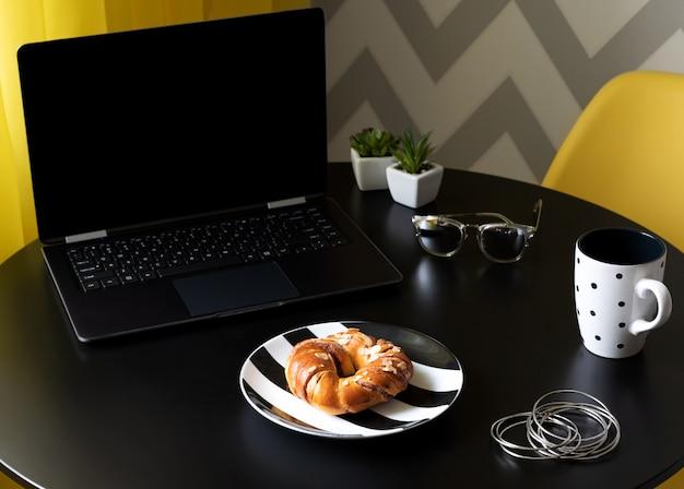 Tavolo da cucina nero moderno con accessori per laptop, tazza di caffè e donna
