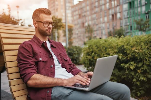 Moderno blogger vista laterale del giovane bell'uomo con la barba in abiti casual e occhiali da vista