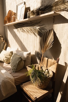 Interior design moderno in stile boho. decorazioni della camera da letto bohemien. calde ombre del sole sul muro