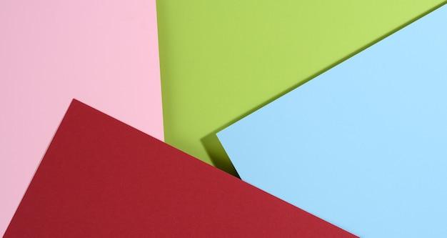 Sfondo luminoso moderno con fogli di carta blu e rosa, rossi e verdi con ombra. modello di business, disposizione piatta