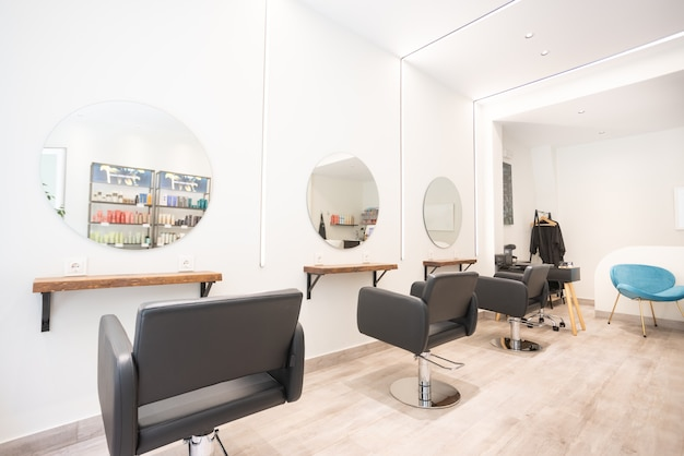 Moderno e luminoso salone di bellezza per parrucchieri interni con sedie nere, specchi rotondi e luci al neon