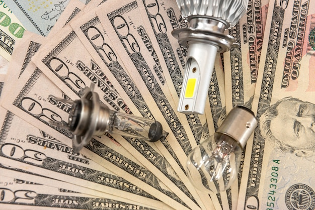 Lampadina luminosa moderna dell'automobile della lampada sul fondo del dollaro, concetto di vendita