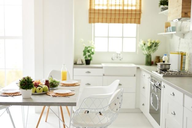 Interno bianco luminoso moderno della cucina con la prima colazione sana dei dettagli di legno e bianchi con la frutta e