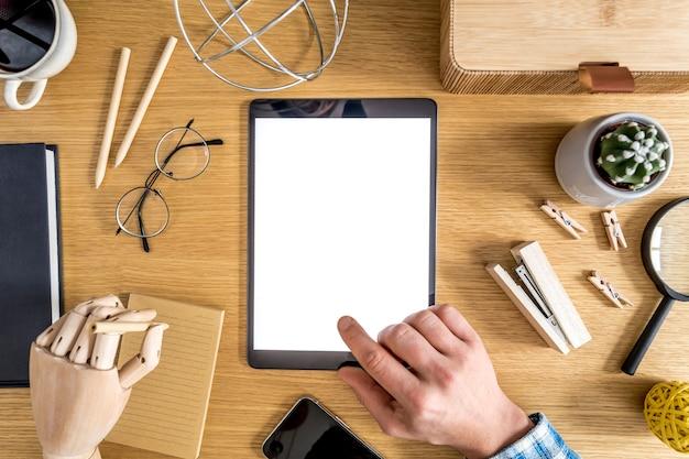 Composizione aziendale moderna in ufficio a casa con freelance, schermo tablet mock up, pianta, note, telefono cellulare e forniture per ufficio in un elegante concetto di arredamento per la casa.