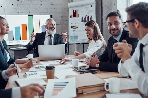 Uomini d'affari moderni che comunicano tra loro mentre lavorano insieme nella sala riunioni