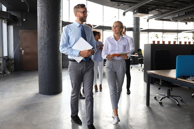 Gli uomini d'affari moderni discutono mentre camminano per l'ufficio.