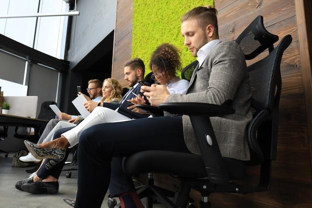 Uomini d'affari moderni in attesa di colloquio di lavoro.