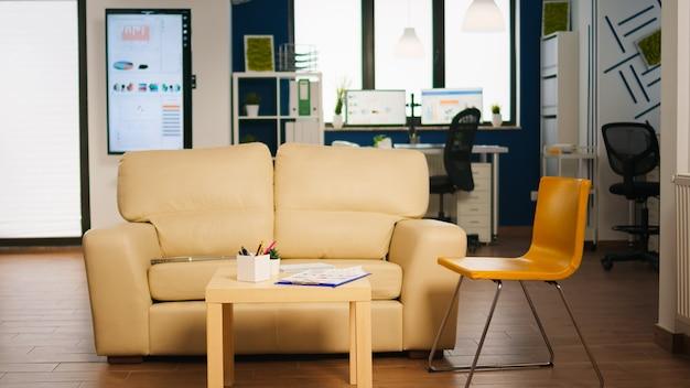 Interni di zona relax business moderno con comodo divano e sedia arancione. area di sosta nel centro affari con un piccolo divano, inquadratura di una stanza vuota con mobili moderni, scaffali bianchi e pareti blu.