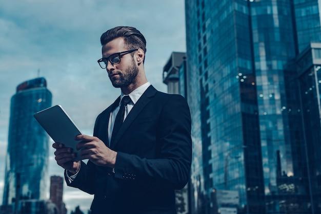 Uomo d'affari moderno in città. immagine notturna di un giovane fiducioso in completo