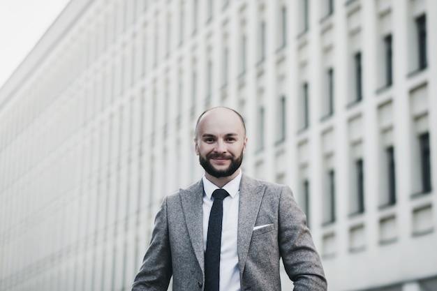Uomo d'affari moderno. fiducioso giovane in tuta in piedi all'aperto con il paesaggio urbano in background