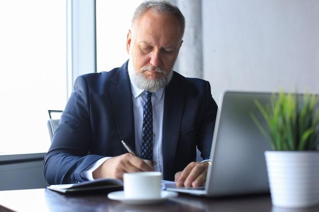 Uomo d'affari moderno che pensa a qualcosa mentre è seduto in ufficio.