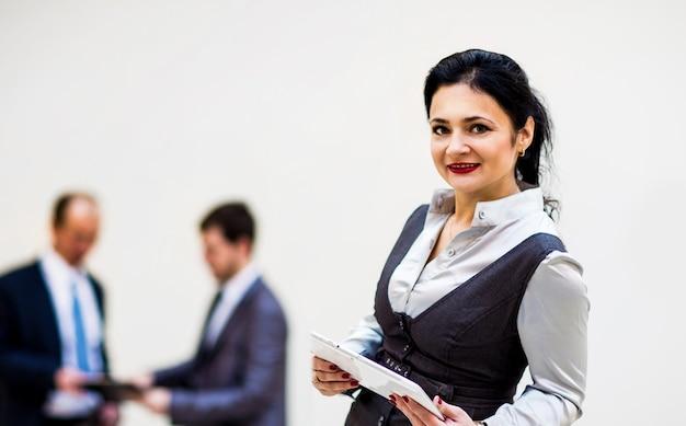 Donna d'affari moderna che tiene computer tablet con un collega sullo sfondo?