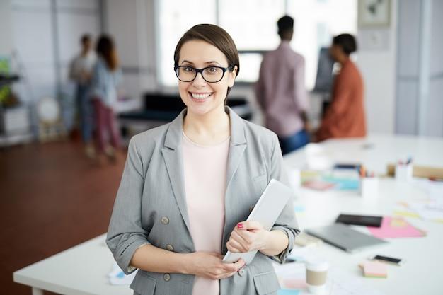 Donna di affari moderna che propone nell'ufficio