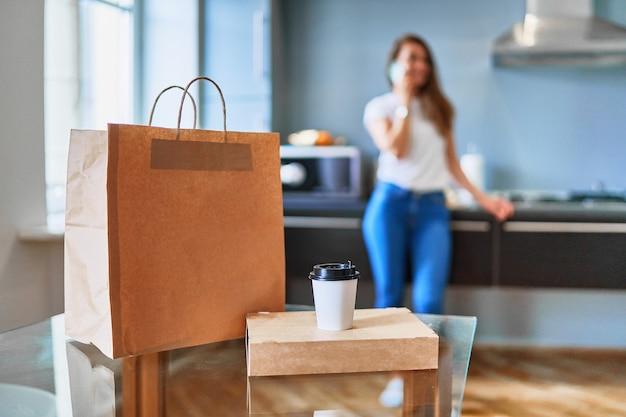 Il cliente di giovane donna felice adulto casual moderno occupato ha ricevuto sacchetti di cartone con cibo e bevande da asporto a casa. concetto di servizio di consegna veloce