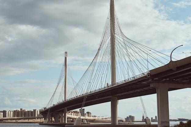 Ponte strallato moderno sopra il fiume contro il cielo nuvoloso. primo piano di costruzione di ingegneria