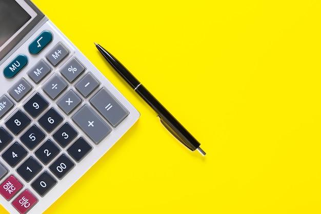 Calcolatrice moderna e penna sulla superficie del colore
