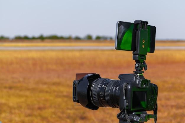 Fotocamera moderna su un treppiede sul campo