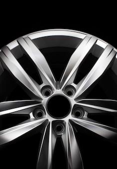 Ruota in lega di alluminio auto moderna isolata su sfondo scuro.