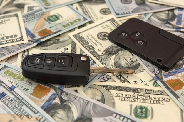 Chiave dell'automobile moderna con il concetto di dollaro, vendita o affitto