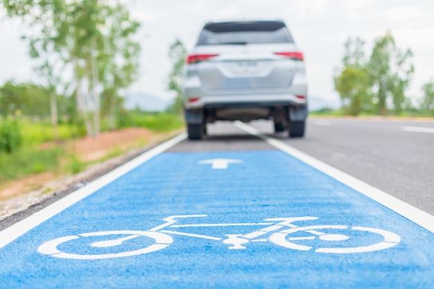 Automobile moderna che funziona sul segno bianco della bicicletta