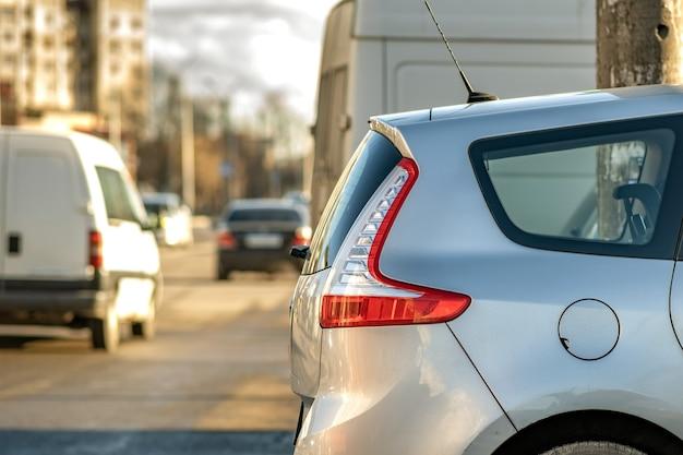 Auto moderne parcheggiate su un lato di una strada cittadina.