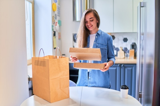Il cliente di una giovane donna millenaria sorridente felice adulta e casual moderna ha ricevuto sacchetti di cartone con cibo e bevande da asporto a casa. concetto di servizio di consegna veloce