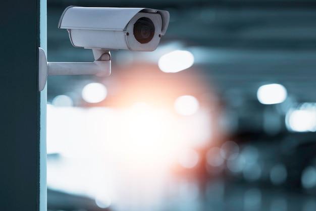 Moderna telecamera cctv per il monitoraggio della sorveglianza e della sicurezza sul muro con lo sfondo del parcheggio.