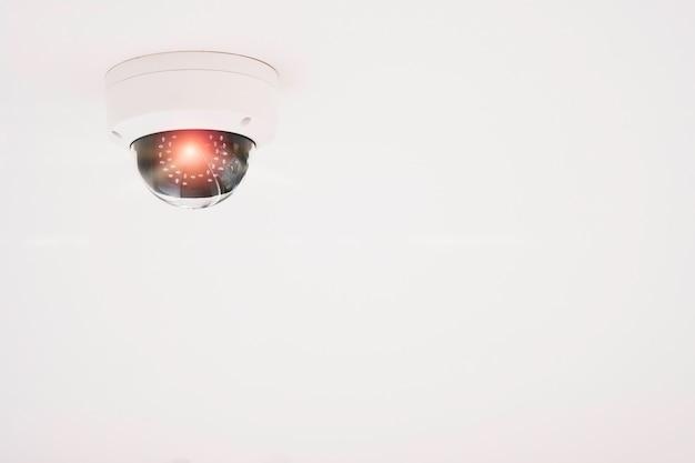 Moderna telecamera cctv per il monitoraggio della sorveglianza e della sicurezza sul soffitto bianco.