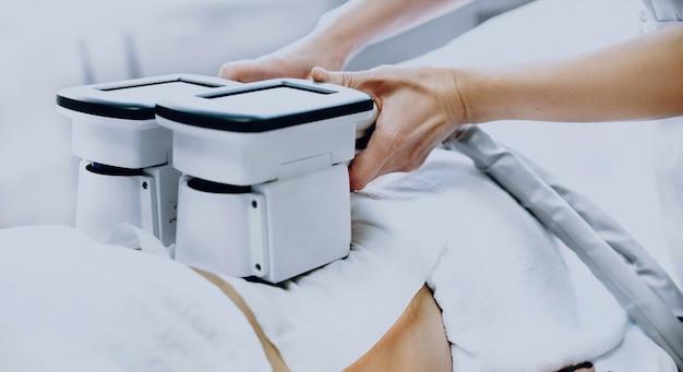 Moderna sessione di trattamento della cellulite eseguita da un medico in una clinica professionale