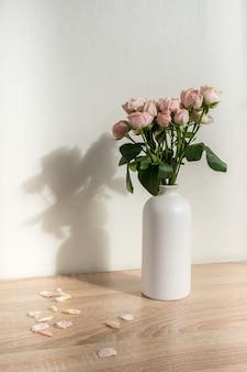Vaso moderno in ceramica con rose sfondo muro bianco interni scandinavi