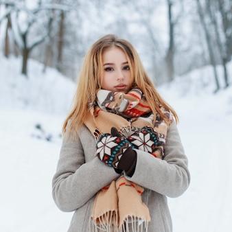 Moderna affascinante giovane ragazza in un cappotto caldo vintage in bellissimi guanti di lana con una sciarpa alla moda con un motivo rosso in posa all'aperto