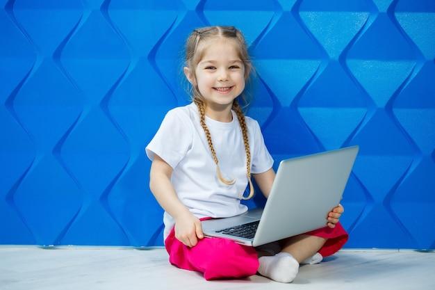 Una moderna bambina usa un laptop sdraiato sul pavimento con le gambe che guardano la telecamera. bambino divertente su uno sfondo di parete blu brillante. moderna tecnologia wireless per internet