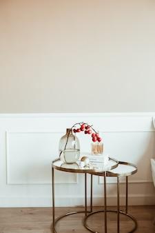 Interior design classico moderno. soggiorno decorato. comodino con bouquet di bacche rosse in vaso di vetro, libro, candela davanti al muro beige