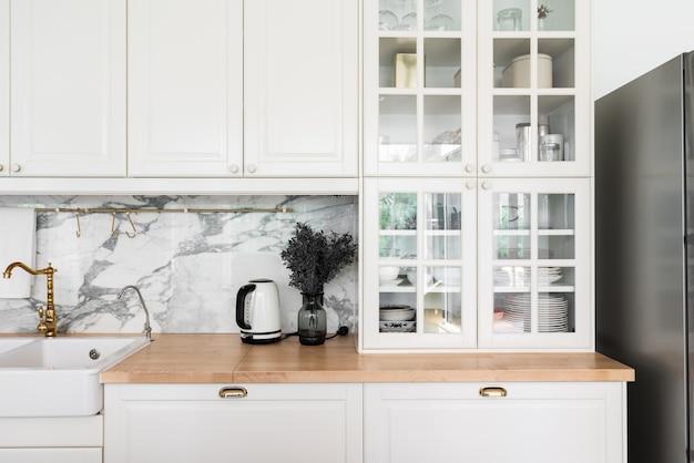 Interno di cucina classica moderna con elettrodomestici da cucina e lavello in ceramica bianca con rubinetto a specchio dorato su piano in legno con parete in marmo