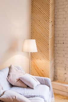 Decorazione moderna e pulita di un appartamento con un divano e una lampada