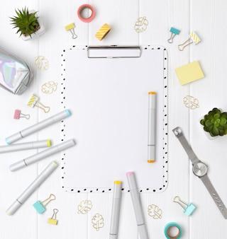 Appunti moderni con foglio bianco e pennarelli, clip, leganti nastro adesivo e piante su un tavolo di legno bianco.