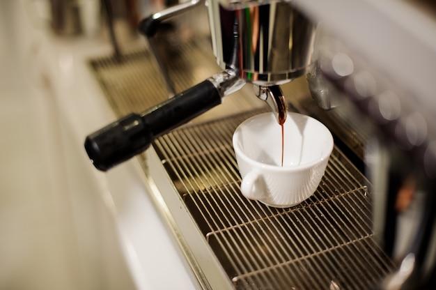 Macchinetta per caffè moderna che versa un caffè fresco e aromatico in una tazza