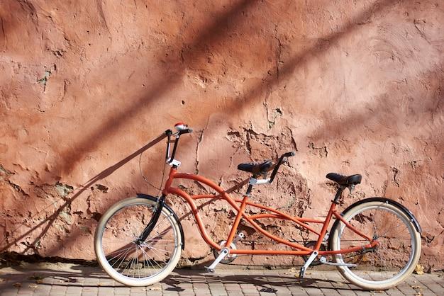 Moderna confortevole doppia bicicletta tandem arancione con ruote bianche sul marciapiede vuoto pavimentato appoggiato contro il vecchio muro rosso incrinato intonacato in una luminosa giornata di sole estivo