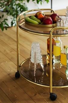 Composizione moderna di bar da cucina in oro con diverse bevande, frutta, decorazioni ed eleganti accessori personali. modello.