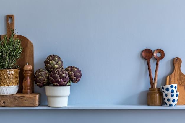 Composizione moderna all'interno della cucina con tagliere di verdure, cibo, erbe aromatiche, accessori da cucina e spazio copia sullo scaffale.