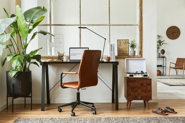 Composizione moderna dell'interior design maschile dell'area di lavoro dell'ufficio domestico con scrivania industriale nera, poltrona in pelle marrone, laptop, giradischi vintage e accessori personali eleganti. modello.