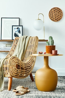 Composizione moderna in un elegante soggiorno con poltrona di design, tavolino da caffè giallo, cornici per poster finte, moquette, decorazioni, cactus e accessori eleganti nell'arredamento della casa