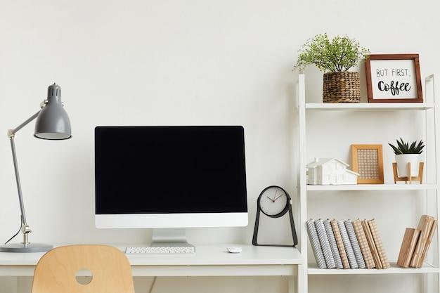 Computer moderno sulla scrivania contro il muro bianco all'interno dell'ufficio domestico