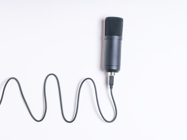 Un moderno microfono a condensatore con un filo su sfondo bianco. apparecchiature per la registrazione del suono.