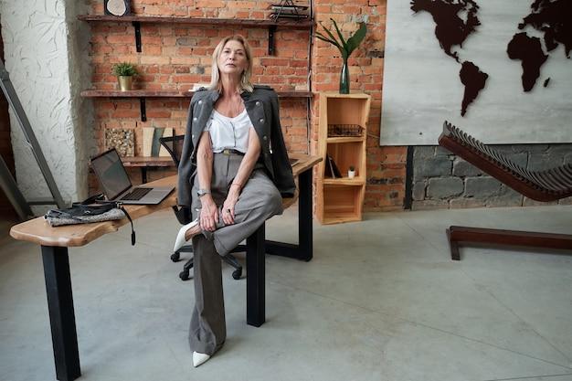 Donna matura sicura moderna in vestito alla moda che si siede sul tavolo e in posa